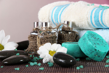 Oil spa towels on bamboo mat on gray background