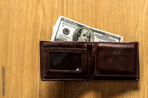 Wallet with money on wooden background