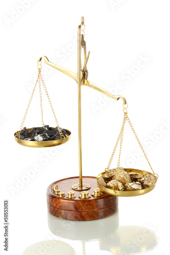 Gold and coal on scales isolated on white