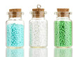 Little bottles full with colorful beads isolated on white