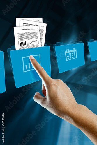 a finger of a woman, selects and opens a folder