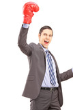 A happy young businessman with red boxing gloves gesturing happi