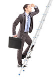 Full length portrait of a businessman with  briefcase climbing a