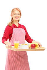 A smiling mature woman in apron carrying a tray with drinks and