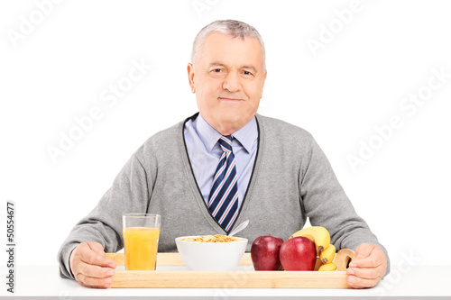 A gentleman sitting on a table with a tray full of drinks and fo