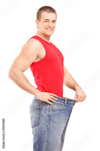 A satisfied weight loss man in a pair of old jeans
