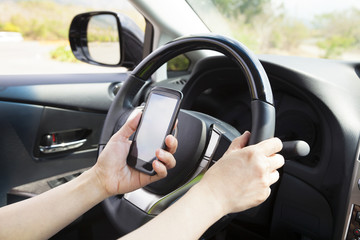 smart phone in hand  while driving the car