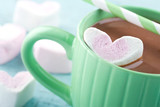 Hot chocolate in a green cup and marshmallows