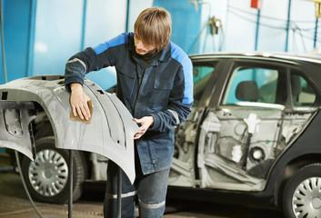 repairman sanding plastic car bumper