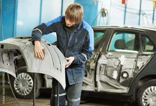 repairman sanding plastic car bumper - 50559465