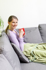 Woman sitting in a living room while drinking coffee