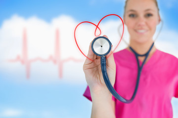 Happy nurse holding up stethoscope to heart design
