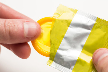 Hand pulling yellow condom from wrapper