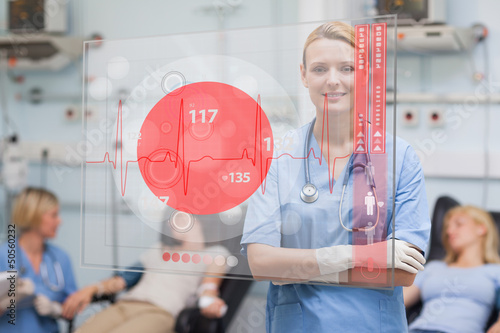 Smiling nurse standing behind red ECG display screen