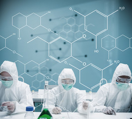 Chemists working in protective suit with futuristic interface sh