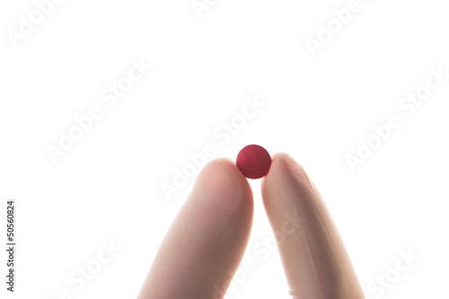 Gloved hand holding red tablet