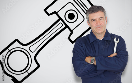 Mature mechanic standing next to car symbol