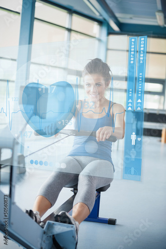 Young girl doing rowing machine with futuristic interface