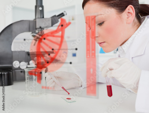 Scientist pouring drop of blood onto glass with futuristic inter