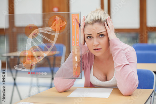 Blonde woman thinking hard while studying on interface with DNA