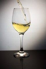 White wine being poured into clear wine glass