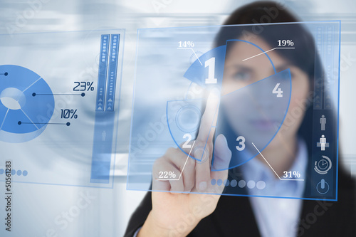 Serious businesswoman using blue pie chart futuristic interface