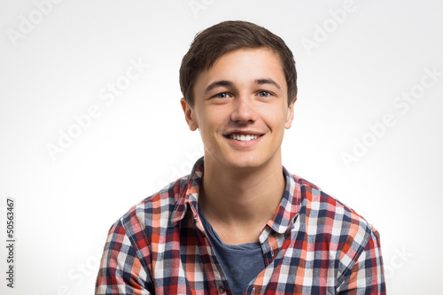 Junger Mann grinst in die Kamera