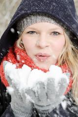 junge blonde Frau pustet in einen handvoll Schnee