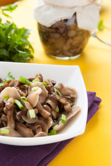 pickled honey mushrooms and green onions in a white bowl