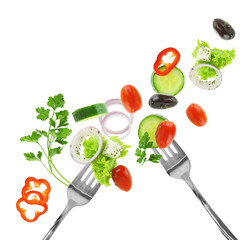 Fresh mixed vegetables and silver forks isolated on white