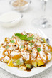 fruit salad with nuts, yogurt and mint, vertical closeup