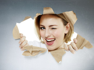 Woman blinks one´s eyes looking through paper hole