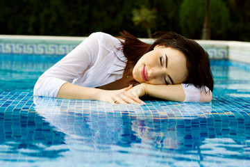 beautiful long hair female model posing by the pool