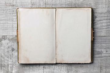 Altes Buch mit leeren Seiten vor Holzhintergrund