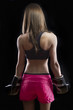 Beautiful woman kick boxing over dark background