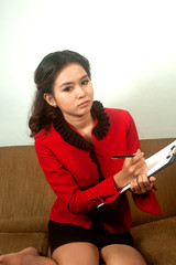 Asian woman wearing red suit holding and writing paper with cli