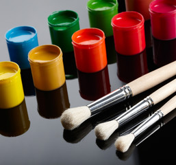 Paint buckets with paintbrushes over dark background