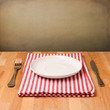 Empty plate with silverware on tablecloth on wooden table