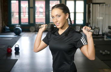 Attractive Young Brunette Woman Lifts Ten Pound Barbells at Gym