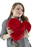 Beautyful young and smiling woman embraces heart shaped pillow