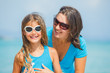 Mother and her daughter in sunglasses on beach