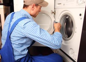 Handwerker repariert Waschmaschine Seitenansicht