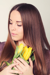 Beautiful woman with long hair with yellow tulips