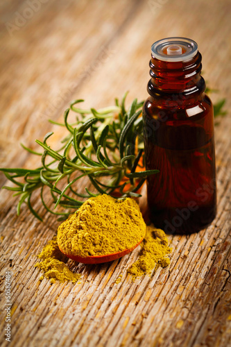 Bottle of aromatic essence oil, fresh and powdered rosemary