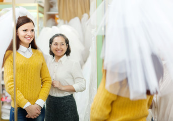 Shop assistant  helps the bride in choosing bridal veil