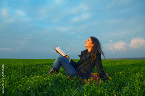 Teen girl reading the Bible outdoors