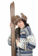 young woman in winter clothes holding old wooden skis