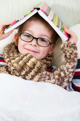 Cute little bpo in glasses with book above head