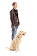 Full length portrait of a young man standing with a retriever do