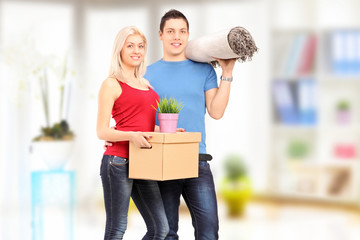 Full length portrait of a young male and female holding a moving